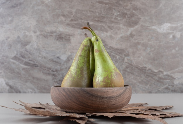 A small bowl of pears on plane tree leaves on marble
