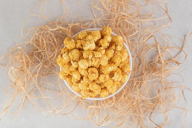 Ciotola piccola posta sopra una pila di paglia e riempita con popcorn canditi su un tavolo di marmo.