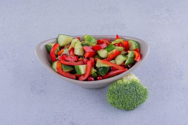 Piccola ciotola di insalata accanto a un pezzo di broccoli su sfondo marmo. foto di alta qualità