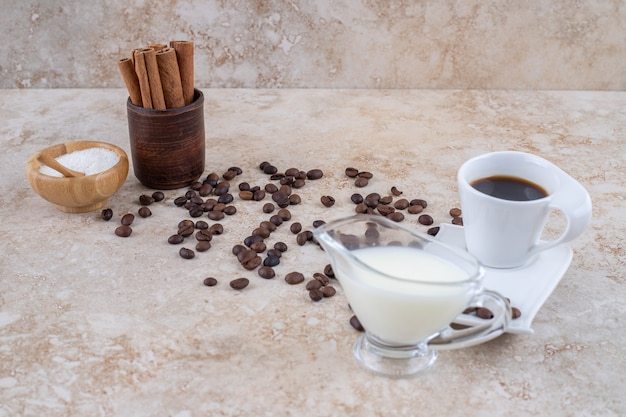 Una piccola ciotola di zucchero e bastoncini di cannella in una tazza di legno accanto a chicchi di caffè sparsi, che serve un bicchiere di latte e una tazza di caffè
