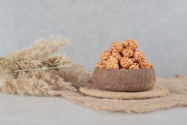Piccola ciotola su un sottopentola con una porzione di caramelle popcorn accanto a gambi di aguglia sul tavolo di marmo.