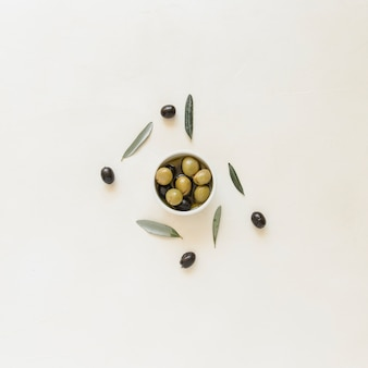 Small bowl with olives and leaves