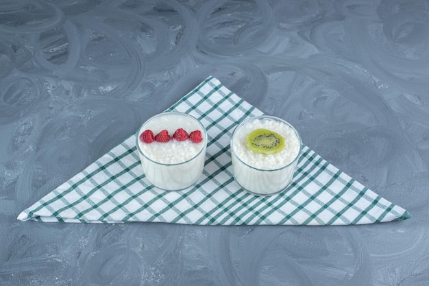 Small bowls of milky rice garnished with raspberries and kiwi slice on a tablecloth on marble table.