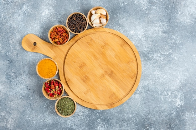Small bowls of spices around wooden board.