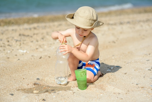 A small boy alone plays on the seashore wearing a hat and striped shorts heat