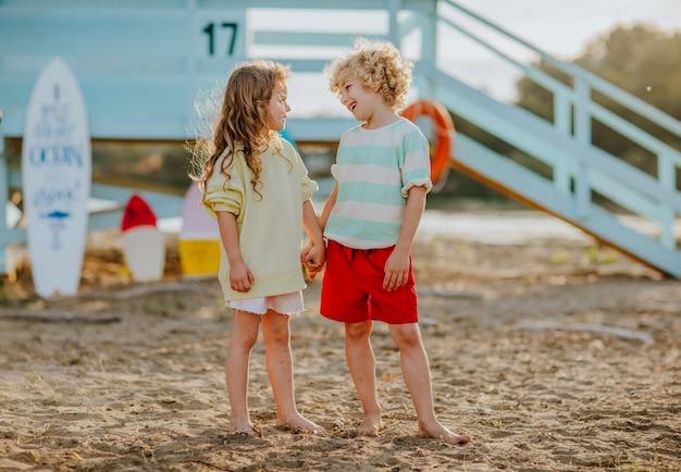 ライフガードタワーを背景にビーチで手をつないで夏服の小さな男の子と女の子