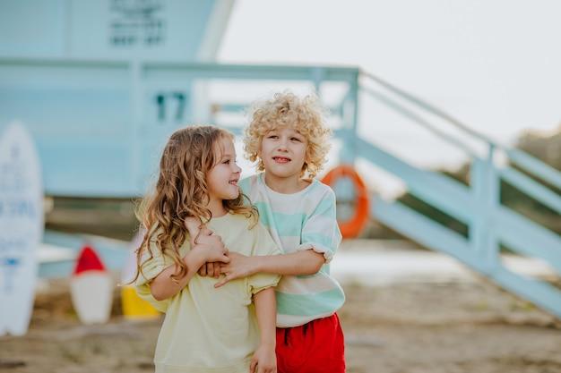 ライフガードタワーを背景にビーチで抱き締める夏服の小さな男の子と女の子