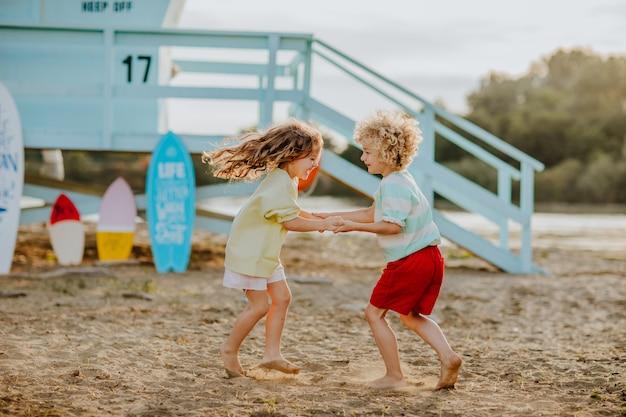 ライフガードタワーを背景にビーチで遊ぶ夏服の小さな男の子と女の子
