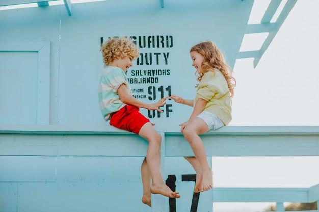 ビーチのライフガードタワーに座っている夏服の小さな男の子と女の子