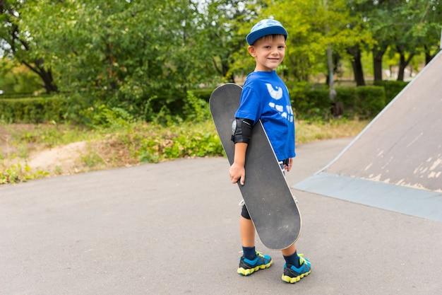 スケートパークでスケートボードを持って、コンクリートのスロープの底でカメラに向かって微笑む小さな男の子