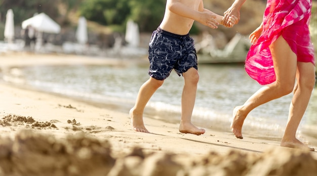 Small boy child and young woman together running next to the sea sand beach holding hands ,blurred background, travel concept, copy space