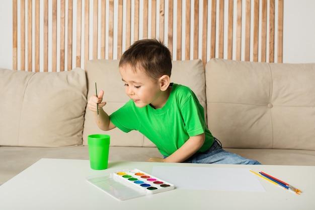 작은 소년은 방에있는 테이블에 종이에 붓과 페인트로 그립니다.