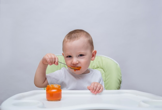 A small boy eats mashed carrots at a table and looks at the camera on a white isolated