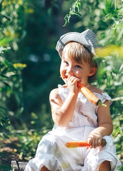 Small boy farmer kid sitting in line of tomatoes plants, wearing white casual overalls suit and grey hat