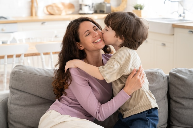 Маленький мальчик нежно целует маму в щеку, обнимая мать-одиночку в день матери или поздравляя с днем рождения. милый сын 5, обнимая любящую маму, показывает любовь и заботу. концепция отцовства и счастливой семьи