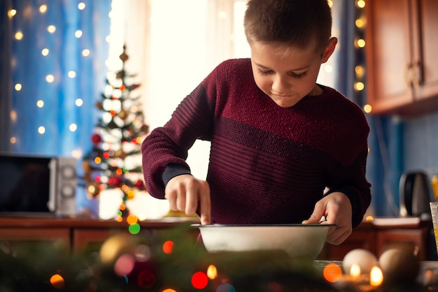 크리스마스 비스킷을 요리하는 그의 엄마를 돕는 작은 소년
