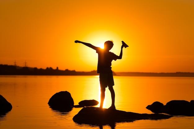 작은 소년은 강가에서 손에 종이 비행기를 들고 있습니다. 여름에 아름 다운 오렌지 일몰입니다. 호수 근처에 종이접기 비행기가 서 있는 소년의 실루엣.