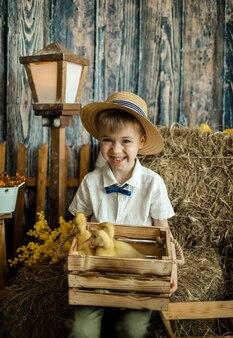 Маленький мальчик в соломенной шляпе и льняной рубашке сидит на стоге сена с деревянным ящиком с утятами. пасха для детей