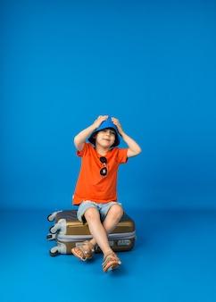 Tシャツとショートパンツとパナマ帽をかぶった小さな男の子は、テキスト用のスペースがある青い表面のスーツケースに座っています
