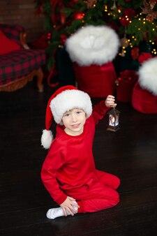 빨간 모자 산타 크리스마스 랜 턴을 들고 작은 소년