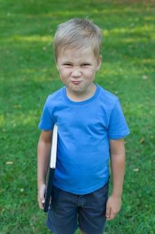 Маленький мальчик в парке стоит и держит в руках книгу.