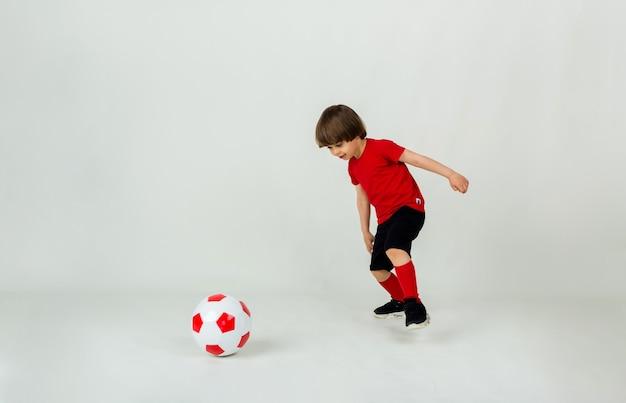 유니폼을 입은 작은 소년은 텍스트를위한 공간이있는 흰색 표면에 축구 공을 가지고 노는