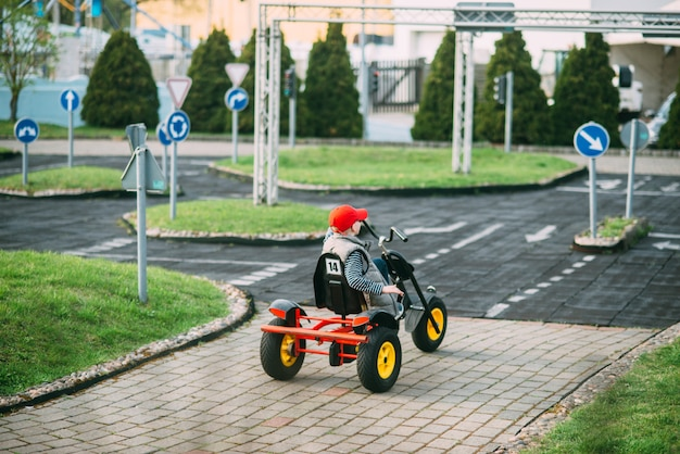 Small boy is driving toy car on the yard