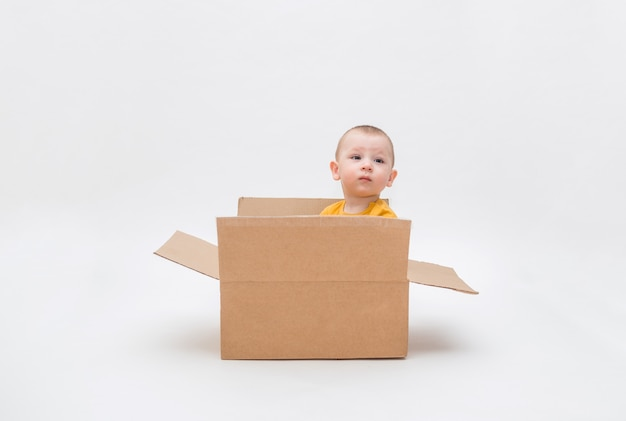 A small boy is sitting in a cardboard box on a white space with an empty seat. a boy in a yellow bodysuit looks . contactless delivery