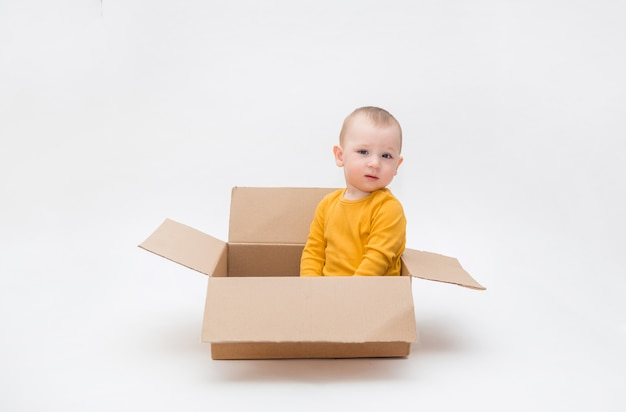 A small boy is sitting in a cardboard box on a white space with an empty space. a boy in a yellow bodysuit looks . contactless delivery