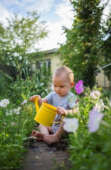A small boy is sitting and holding a yellow watering can in the garden.