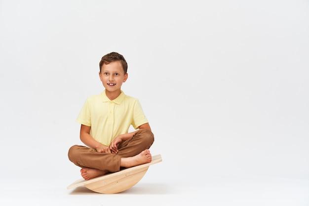 Small boy is sitting on special simulator for training vestibular apparatus.