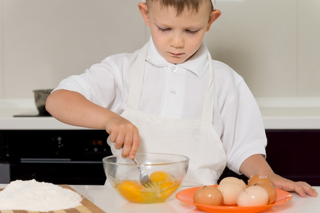 Small boy mixing eggs in a bowl