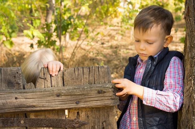 시골을 함께 탐험할 때 금발의 여자 친구를 위해 오래된 소박한 나무 문을 여는 작은 소년