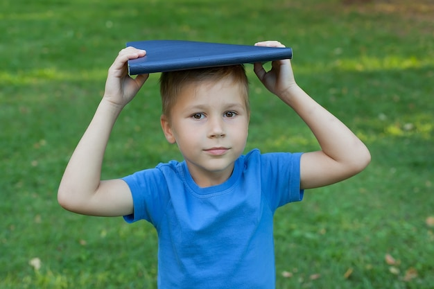 Small boy in the park stands and holds a book on his head.