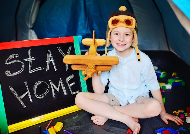 A small boy in a pilot's flight cap with a toy airplane in his hands sits in a tourist tent