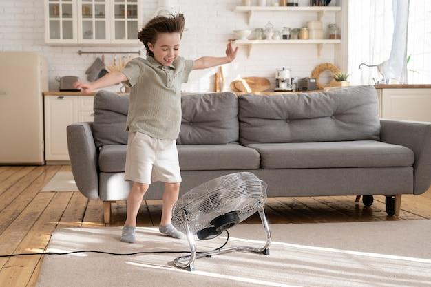 小さな男の子は、居心地の良いリビングルームだけで自宅の人工呼吸器やレトロなファンからの強風で遊ぶ