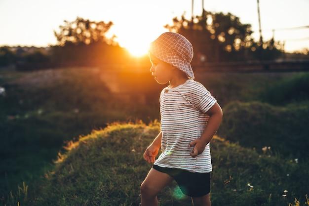 帽子をかぶって太陽が夏の夜に彼を暖めている間、フィールドで遊んでいる小さな男の子
