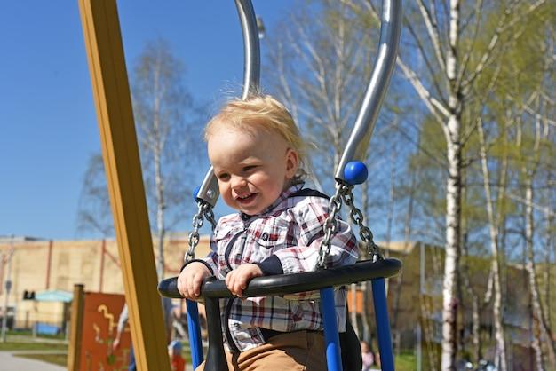 子供の遊び場で遊ぶ小さな男の子。