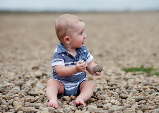 Маленький мальчик играет с камнями на берегу моря