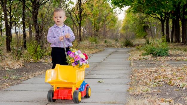 포장 된 국가 차선을 따라 뒷면에 꽃의 꽃다발과 함께 화려한 노란색 장난감 트럭을 따라 당기는 작은 소년