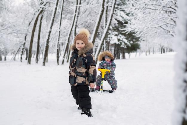 Маленький мальчик тащит свою сестренку на санках.