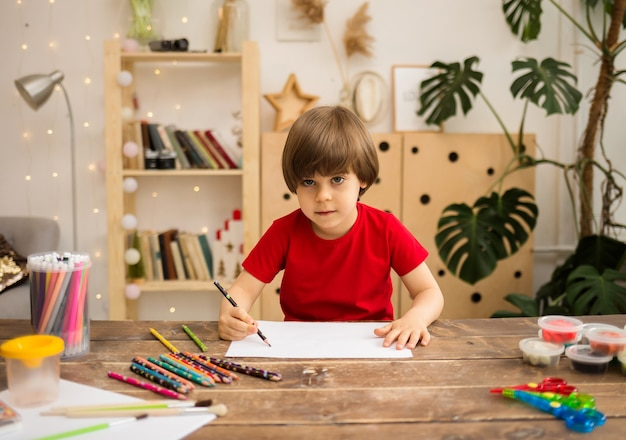 A small boy in a red t-shirt draws with a pencil on white paper at a wooden table