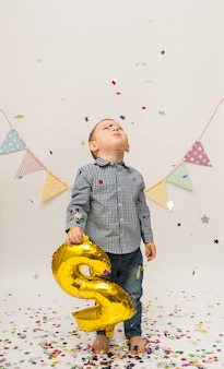 Small boy in a shirt and trousers stands and holds a gold foil number two