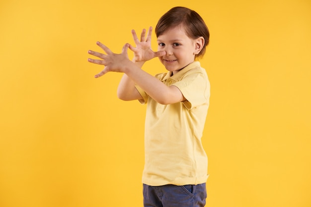 Small boy shows gesture palms at nose.