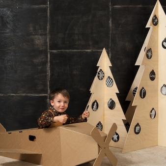 작은 소년은 나무로 만든 크리스마스 트리 근처의 판지 장난감 항공기에 앉아 있다