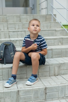 A small boy sits on the steps of the school, holding notebooks and looking up at the sky
