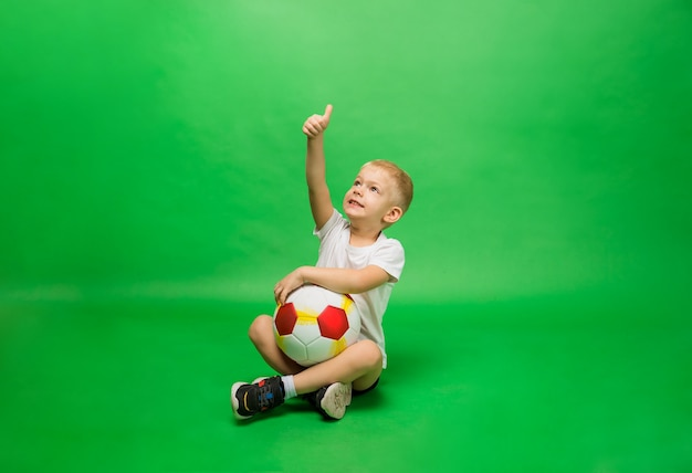 Small boy sits in uniform and with a soccer ball and shows his hand to the class on green