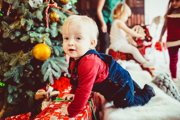 The small boy sitting near christmas tree and presents