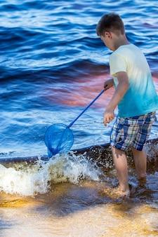 小さな男の子が海に直接漁網を持って立っています。