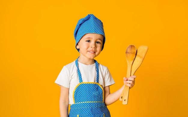 シェフの衣装を着た小さな男の子の幼児は、テキスト用のスペースがある黄色の表面に木のスプーンを持っています